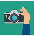 Hand hold retro camera green background design vector image
