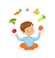 smiling little boy sitting on the floor juggling vector image