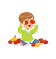 cute little boy sitting on the floor playing with vector image vector image