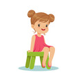 beautiful little girl sitting on a small green vector image