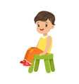 cute little boy sitting on a small green stool vector image