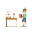 Boy Holding A Present Standing Next To Table With vector image