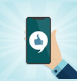 hand holding smartphone with like icon on a screen vector image