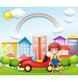 A boy and his red car near the high buildings vector image
