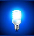 Energy saving light bulb glowing on dark vector image