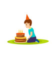 Little boy in festive mood blows out birthday cake vector image