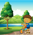 A kid at the riverbank playing with his bicycle vector image