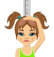 Unhappy little girl measuring her growth in height vector image