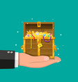 opened chest full of treasures in hand vector image