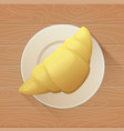tasty buttery croissant on plate and old wooden vector image