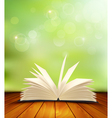 Open book on a wooden floor in front of a green vector image