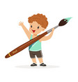 cute smiling little boy holding giant paintbrush vector image vector image