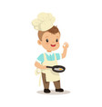cute little boy chef frying egg in a flying pan vector image