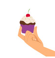 Hand holding cherry cupcake vector image